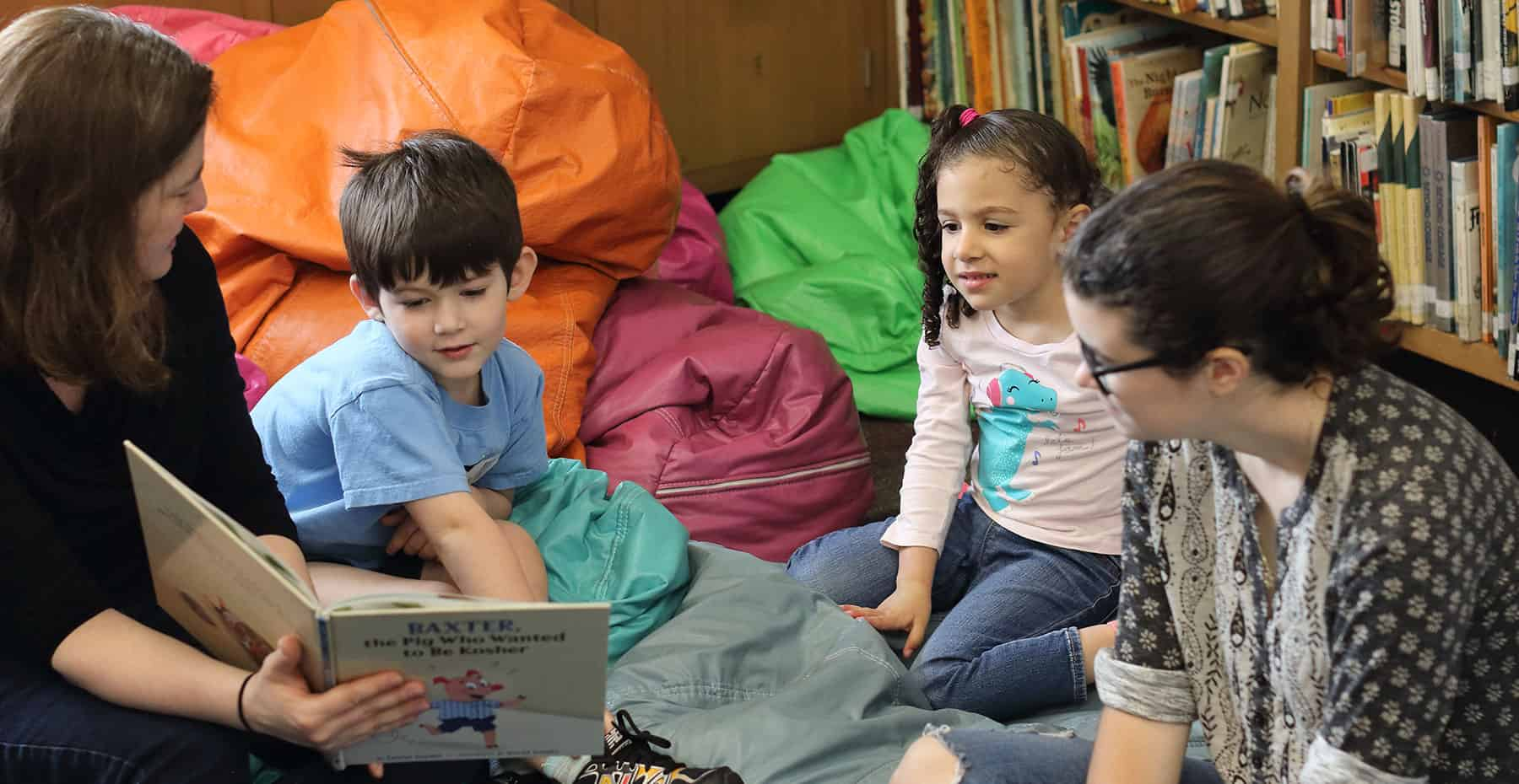 An image of a woman with short brown hair interacting and reading a story to 3 children who sit around, smiling and listening to the book.